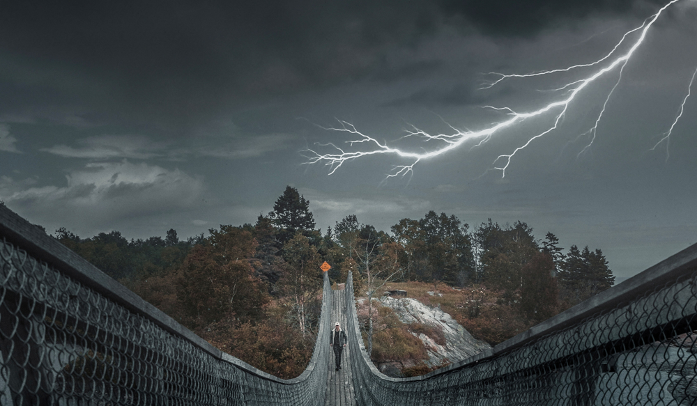 Man walking over a bridge during thunderstom